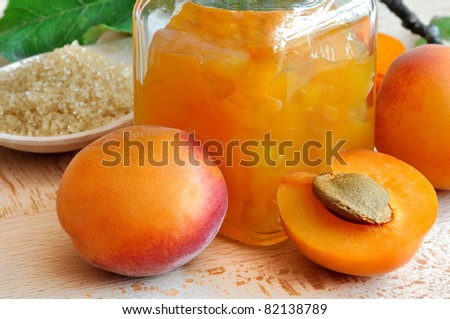 apricot jam and fresh apricots  with  sugar on the wooden table - stock photo