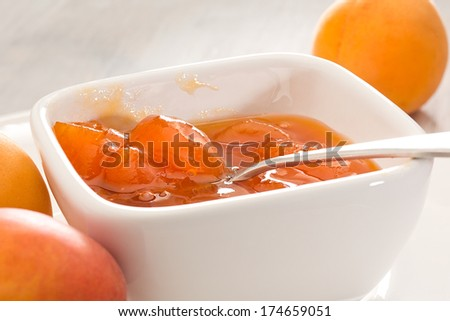 Apricot jam in bowl with metal spoon - stock photo