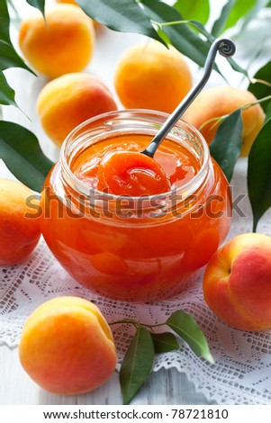 Apricot jam in jar and fresh fruits with leaves - stock photo