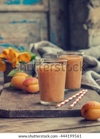 apricot smoothie with yogurt, banana and honey. the basics of proper nutrition. a healthy and delicious Breakfast. wooden textured background, dishes in the rustic style. toned image - stock photo