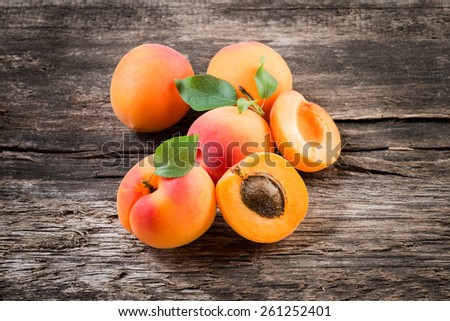 Apricot with leaves on wooden background - stock photo