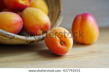Apricots. Fresh ripe apricots in wooden basket on a wooden background. Organic fruit. - stock photo