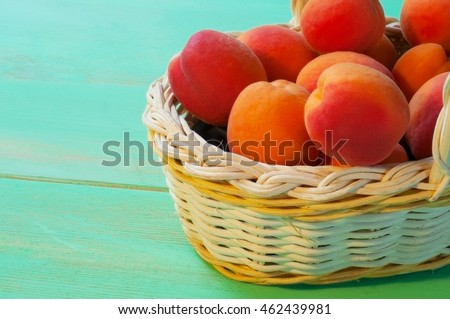 Apricots in basket on wooden background
