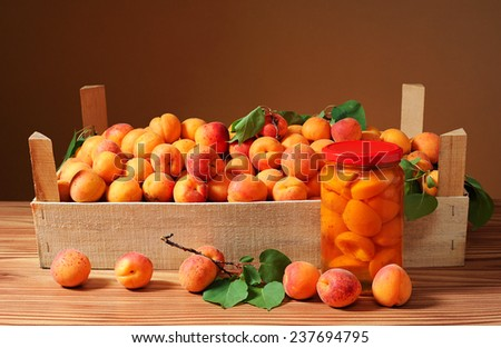 Apricots in wooden crates and compote in a jar of glass - stock photo