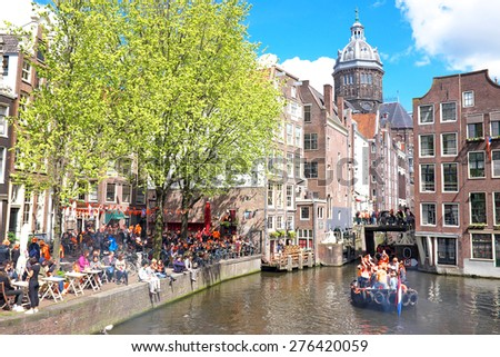 APRIL 27: Amsterdam canals full of boats and people in orange during the celebration of kings day on April 27, 2015 in Amsterdam, The Netherlands - stock photo