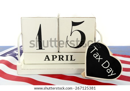 April 15 calendar for USA Tax Day with heart shape sign on USA flag against white background.   - stock photo