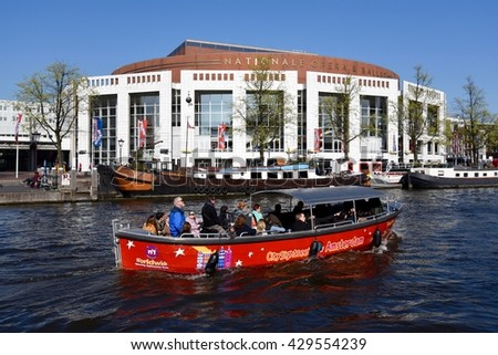 April 10, 2016. Holland, Amsterdam, Opera and ballet theater.  Tourists sailing in a boat.