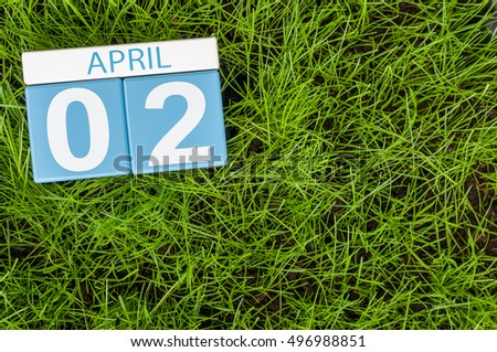 April 2nd. Day 2 of month, calendar on football green grass background. Spring time, empty space for text
