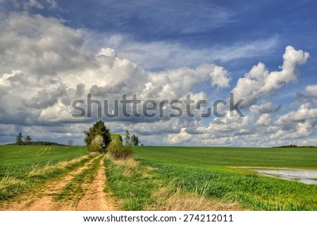 April scenery in the fields with dramatic sky - stock photo