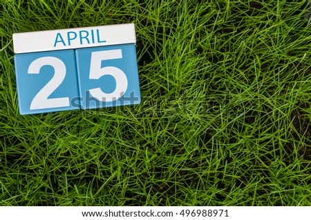 April 25th. Day 25 of month, calendar on football green grass background. Spring time, empty space for text