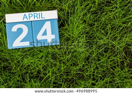 April 24th. Day 24 of month, calendar on football green grass background. Spring time, empty space for text