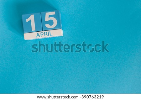 April 15th. Tax Day. Image of april 15 wooden color calendar on blue background.  Spring day, empty space for text - stock photo