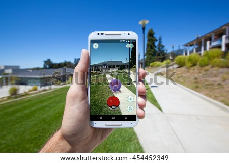 "APTOS, CALIFORNIA - JULY 18, 2016: The hit augmented reality smartphone app ""Pokemon GO"" shows a Pokemon encounter overlain on a college campus in the real world. - stock photo"