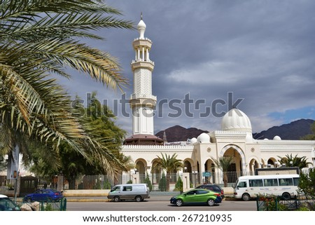 AQABA, JORDAN - MARCH 14, 2014: People near the Al Sharif Hussein Bin Ali mosque in a springtime day. The mosque was built in 1975 and in 2011 was renovated and enlarged - stock photo