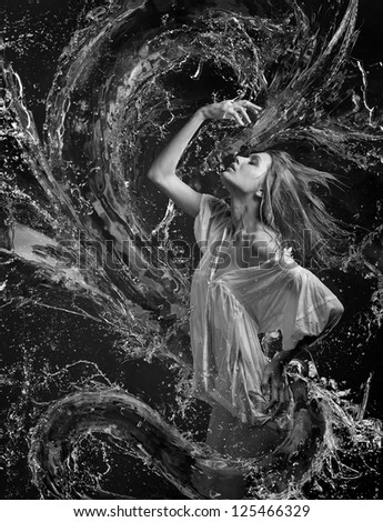 Aqua girl with wet shirt in a spray of water a liquid dragon before her - stock photo