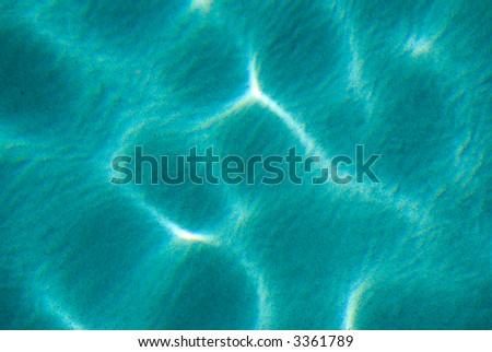 Aqua water with sunlight ripple over sand - stock photo