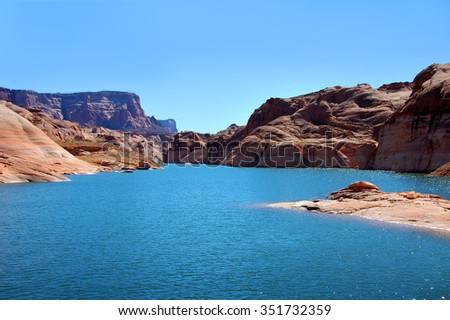 Aqua waters of Lake Powell curve away into the distant Glen Canyon National Recreation Area.  Rock mounds and steep cliffs rise on either side. - stock photo