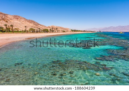 Aquamarine water and underwater corals along empty beach on popular resort of Eilat on Red Sea in Israel. - stock photo
