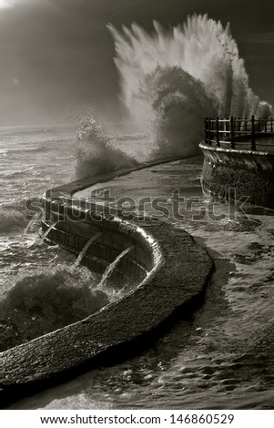 Aquaplosion...The relentless North sea pounds against the winding victorian pathway which becomes in-passable during high tide. - stock photo