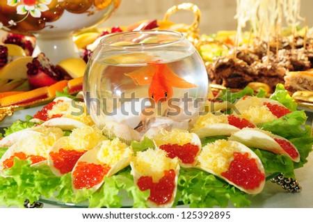 Aquarium fish among party snacks - stock photo