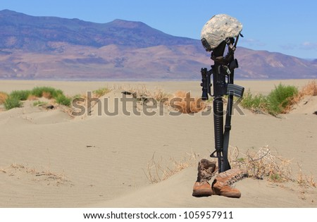 AR-15 rifle, boots and combat helmet mark the grave of a fallen soldier in a desolate land. - stock photo