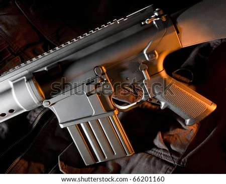 AR-style assault rifle that is lit from the side with orange - stock photo