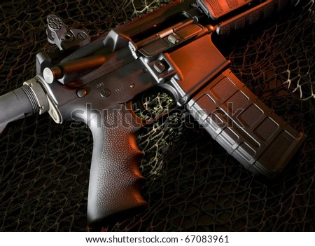 ar-15 that is on a dark background with red lighting - stock photo