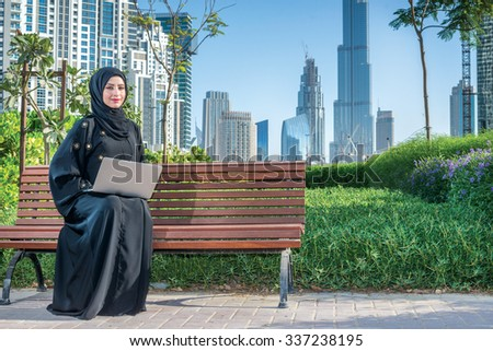 Arab Business. Arab businesswomen in hijab working at a laptop on the background of skyscrapers of Dubai. The woman is dressed in a black abaya - stock photo