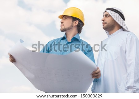 Arab businessman and builder. Low angle view of Arab businessman and builder with blueprint looking away - stock photo