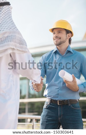 Arab businessman and builder. Low angle view of two men shaking hands - stock photo