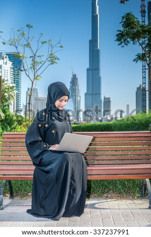 Arab Businesswoman at work. Arab businesswoman hijab working at a laptop on the background of skyscrapers of Dubai. The woman is dressed in a black abaya - stock photo