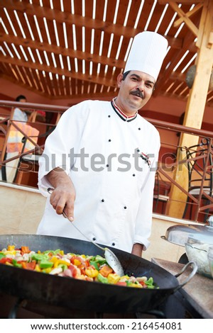 Arab chef in cook uniform frying meat with vegetables on pan outdoors - stock photo