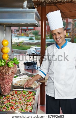 Arab chef in cook uniform making kebab with meat and vegetables - stock photo