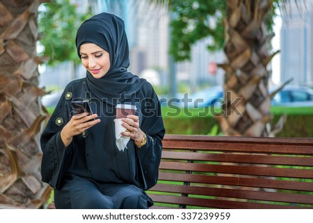 Arab coffee and cell phone. Arab businesswomen in hijab holding coffee outdoors and reading a message on a cell phone against and looking at the camera. The woman is dressed in a black abaya - stock photo