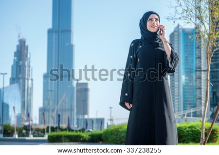 Arab conversation on a cell phone in Dubai. Arab businesswomen in hijab talking on cell phone on the street on a background of skyscrapers of Dubai. The woman is dressed in a black abaya - stock photo