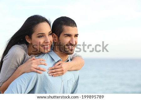 Arab couple flirting piggyback in love on the beach with the sea in the background - stock photo
