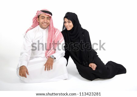 Arab Couple sitting on the floor on white back ground - stock photo