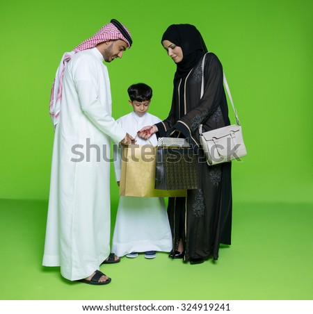 Arab family looking into shopping bags - stock photo