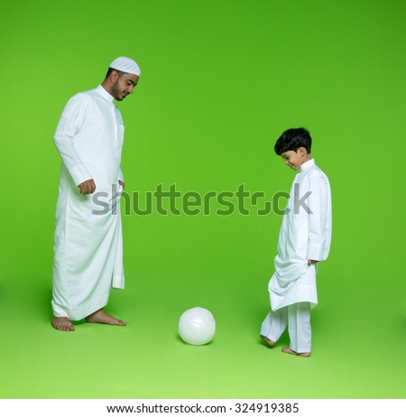 Arab father with son playing football - stock photo