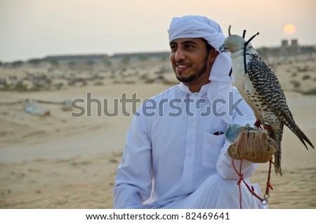 Arab man carrying wild falcon - stock photo