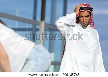 Arab man looking amazed a sexy girl butt in the street with a blue sky in the background - stock photo