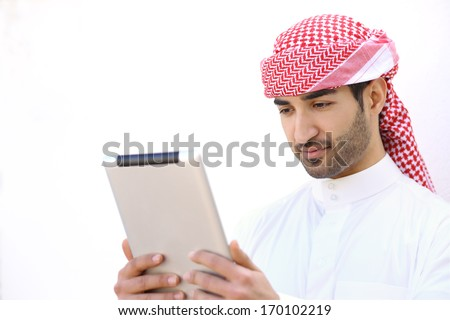 Arab man reading a tablet outdoor on a white wall            - stock photo