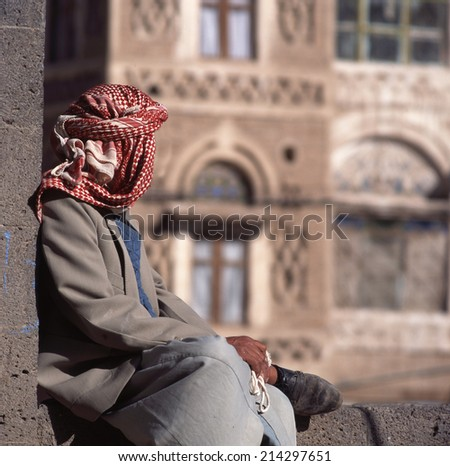 Arab man, seen from the back, with veil. At background typical Yemen house in Sanaa the capital of yemen.  - stock photo