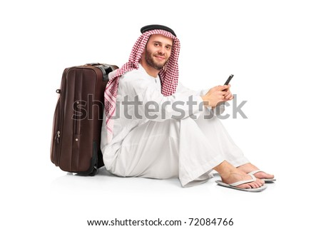 Arab man sitting near a suitcase and typing a text message on his cellphone isolated on white background - stock photo