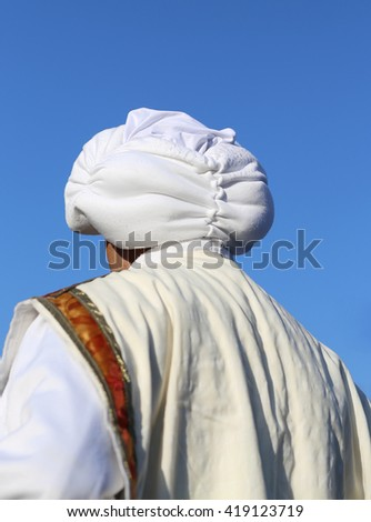 Arab man with white turban and blue sky in background - stock photo