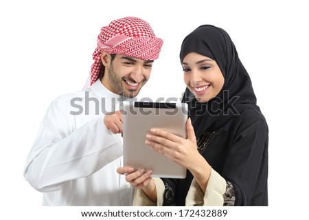 Arab saudi happy couple browsing a tablet reader isolated on a white background             - stock photo