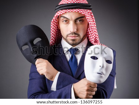 Arab with masks in dark studio - stock photo