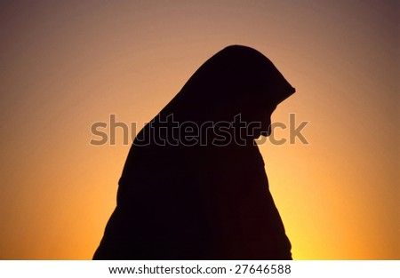 Arab woman with Islamic headscarf in back light