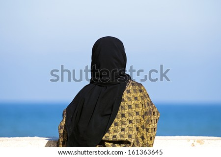 Arab woman with Islamic headscarf looking over the ocean - stock photo