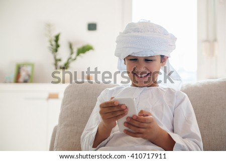 Arabian Boy Using Smartphone At Home - stock photo